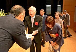 表彰状を受け取る山邊信弘さん・節子さん夫婦=神埼市千代田文化会館はんぎーホール