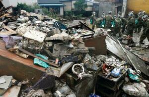 泥まみれで積み上げられた家財道具など=12日午前8時26分、熊本県人吉市