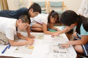 選んだ記事でオリジナルの新聞紙面を作る富士小6年の子どもたち=佐賀市富士町の笹沢左保記念館