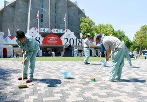デッキブラシで地面の汚れを落とす参加者たち=佐賀市の幕末維新記念館前