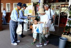 交通安全啓発のチラシや飲料水などを配り、安全運転を呼び掛けた=佐賀市の道の駅「大和」