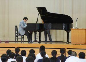 母校でピアノを演奏する徳永義昭さん=佐賀市の川副中