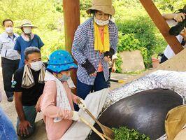熱くなった釜で茶葉を炒る参加者=神埼市脊振町の高取山公園