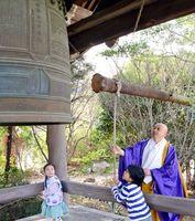 追悼の鐘の音を響かせた山口副住職ら=鹿島市の誕生院