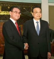 中国の李克強首相(右)と握手する河野外相=15日、北京の中南海(共同)
