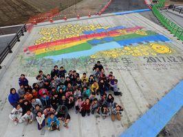 工事中の橋に描かれた虹の上を走るトロッコと、北方小の3年生=武雄市北方町の武雄バイパス工事現場(国交省佐賀国道事務所提供)