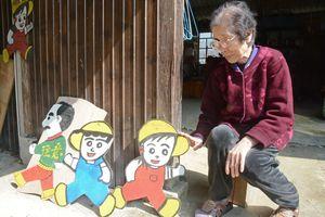 リバーシブルの裏表と高齢者用「アッちゃん人形」と江越久枝さん=佐賀市の自宅