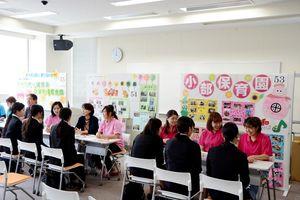 保育施設担当者の説明を聞く学生たち(手前)=佐賀市神園の西九州大佐賀キャンパス