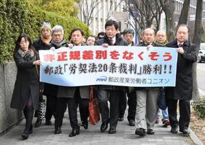 日本郵便の待遇格差を巡る訴訟の判決で、大阪地裁に向かう原告ら=21日午後