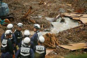 朝方までに降った雨で水量が増えた熊本県津奈木町の土砂崩れ現場。手前は行方不明者捜索の準備をする警察官=11日午前9時14分