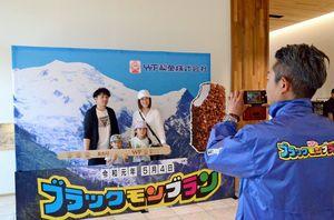 フォトスポットで特大当たり棒を手に記念撮影する家族連れ=佐賀市のJONAI SQUARE