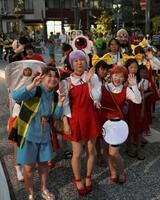 夕暮れの「水木しげるロード」を、ねこ娘など妖怪の仮装でパレードする参加者=17日、鳥取県境港市