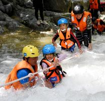 「2018国際渓流滝登りinななやま」で、ロープを頼りに恐る恐る激流を渡る参加者=昨年8月、唐津市七山
