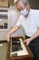 「選定保存技術」への追加が検討されている三味線の製造修理の現場で部品を運ぶ人=2020年7月、東京都八王子市