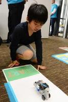 自分たちでプログラミングした自動車型のロボットをコース上で走らせる参加者=小城市のゆめぷらっと小城