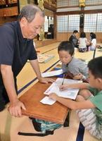 お年寄りや住職が先生になって子どもたちの宿題にアドバイスを送る寺子屋=基山町長野の光蓮寺
