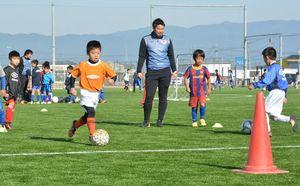 サガン鳥栖のコーチからドリブルの指導を受ける小学生=佐賀市北川副町の龍谷学園グラウンド