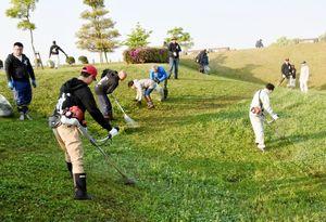 草刈り機で周辺の雑草を刈る参加者たち=佐賀市の三重津海軍所跡