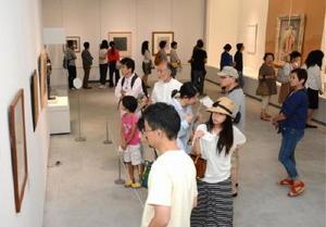 絵画や版画、ブロンズなどさまざまなピカソの作品を熱心に鑑賞する来場者=佐賀市の佐賀県立美術館