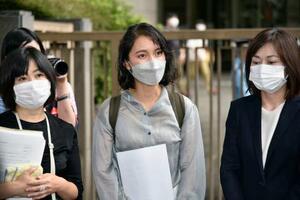 第1回口頭弁論を終え、報道陣の取材に応じる伊藤詩織さん(中央)=21日午前、東京高裁前