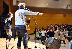 谷口國博さん(左から2人目)の「やっぱノリノリー!」に合わせて踊る園児たち=佐賀市のエスプラッツ