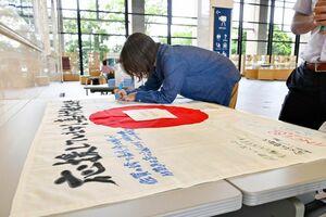 嘉村健士選手への応援メッセージをフラッグに記入する女性=佐賀県庁