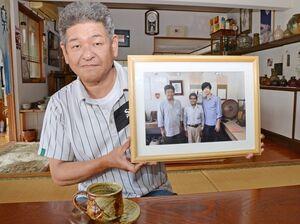 三浦春馬さんと一緒に撮った写真を持つ金子晃久さん。手前は三浦さんが購入したコーヒーカップ=武雄市武内町の金子窯