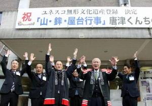 「山・鉾・屋台行事」の無形文化遺産登録決定を祝い万歳する「唐津くんち」の関係者=1日午前、唐津市役所