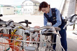 無施錠の自転車に特製の札をつける署員=神埼市の神埼中学校