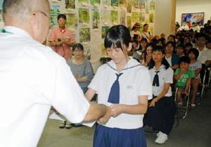 田代代表から賞状と記念品を受け取る藤松さん(右)=佐賀市の県立博物館