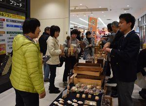手話や筆談などを交えながら接客する生徒=佐賀市のコープさが新栄店