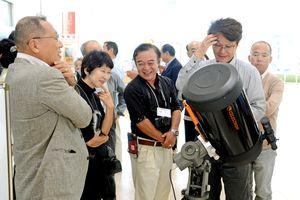 最新式の望遠鏡を囲む参加者ら=佐賀市松原のバルーンミュージアム