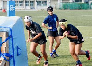 タックル練習に励む佐賀工高ラグビー部の女子選手たち=佐賀市の同校