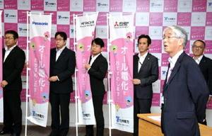 オール電化の販促キャンペーンで使うのぼり旗の前で、営業再開の狙いを語る九電の渡辺義朗常務(手前右)=福岡市の電気ビル共創館