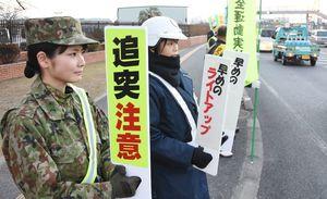 安全運転を呼びかけた自衛隊の隊員と神埼署の署員ら=吉野ヶ里町の目達原駐屯地前