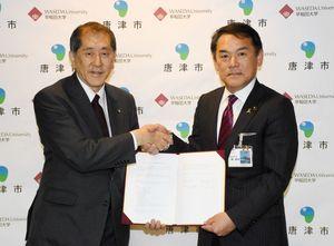 協働連携の協定を結んだ早稲田大学の田中愛治総長(左)と峰達郎唐津市長=唐津市役所
