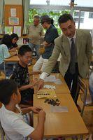 子どもたちに囲碁を指導する吉岡薫八段=有田中部小