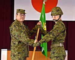佐々木龍太郎隊長(左)から隊旗を受け取る木村登大隊長=神埼郡吉野ヶ里町の目達原駐屯地