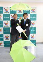 反射材付きの傘を栗原宣康教育長に贈呈したJAからつの堤武彦組合長(左)=唐津市役所大手口別館