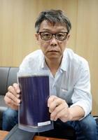 フィルム状太陽電池を手にする川口信弘社長。高温で乾燥するアフリカの過酷な環境に耐えられる設計で、施工も容易という