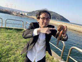 釣り上げたタコを手にする中川淳一郎さん