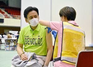 新型コロナウイルスワクチンの接種を受ける山口祥義知事(左)=佐賀市の市村記念体育館