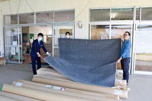 贈られたカーペットを広げる「おもやいボランティアセンター」の鈴木代表(右)とサカイ引越センターの人たち=武雄市の同センター