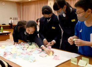 ワークショップで町の魅力や課題を書いた付箋を広用紙に張る中学生=大町町総合福祉保健センター