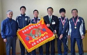 70回大会を記念して新調された優勝旗を携え、優勝報告に訪れた鏡体協チームの関係者と峰市長(右から3人目)=唐津市役所