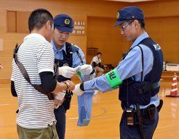 男の所持品検査を行う警察官=佐賀市の県警察学校