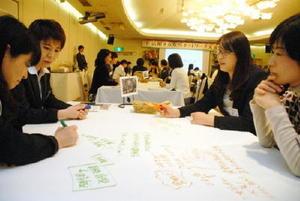 話し合った内容を模造紙に書き込みながら討論する女性ら=佐賀市のマリトピア