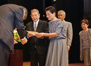 坂田勝次佐賀新聞社常務取締役から表彰を受ける出席者=神埼市千代田町のはんぎーホール