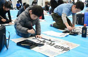 真剣な表情で書き初めに挑む参加者たち=有田町の焱の博記念堂