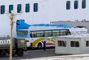 横浜港に停泊中のクルーズ船「ダイヤモンド・プリンセス」に横付けされたバス。この日も船内に残っていた乗員らの一部が下船した=27日午後